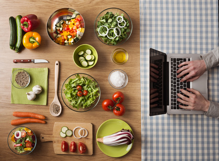 Photo pour Vegetarian healthy food preparation at home on kitchen table with hands typing on a laptop on the right, top view - image libre de droit