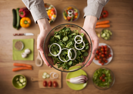 Photo for Hands holding an healthy fresh vegetarian salad in a bowl, fresh raw vegetables  - Royalty Free Image