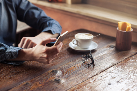 Photo for Young hipster guy texting with his mobile phone at the bar and having a cappuccino - Royalty Free Image