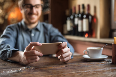 Foto de Cheerful  guy at the restaurant using a mobile phone, hands close up - Imagen libre de derechos