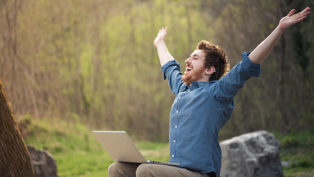 Foto de Happy cheerful  man with a laptop sitting outdoors in nature, freedom and happiness concept - Imagen libre de derechos