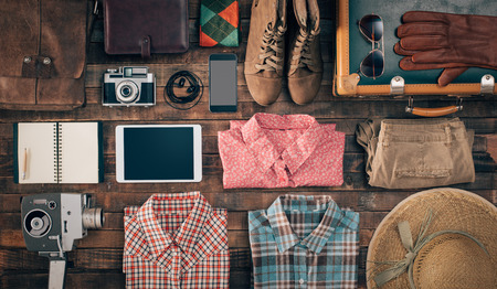 Foto de Hipster vintage accessories and clothing on a wooden table before packing, travel and vacations concept, top view - Imagen libre de derechos