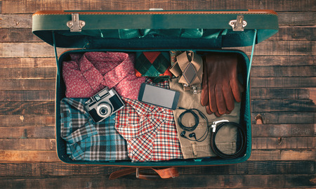 Foto de Vintage hipster traveler packing, open suitcase on a wooden table with clothing, camera and mobile phone, top view - Imagen libre de derechos