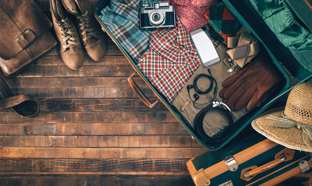 Foto de Vintage hipster suitcase packing before leaving with old suitcase, camera and accessories on a wooden table, top view - Imagen libre de derechos