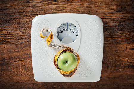 Foto de Green apple wrapped in a tape measure on a white scale, wooden surface on background, dieting and weight loss concept - Imagen libre de derechos