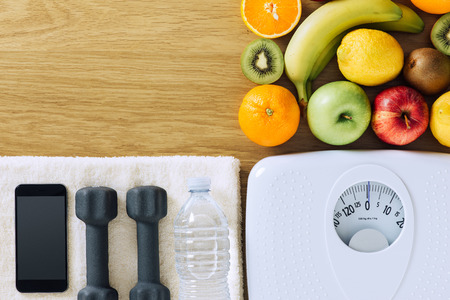 Photo for Fitness and weight loss concept, dumbbells, white scale, towel, fruit and mobile phone on a wooden table, top view - Royalty Free Image