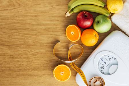 Foto de Healthy eating, fitness and weight loss concept, white scale with fruit on a wooden table, blank copy space at left - Imagen libre de derechos