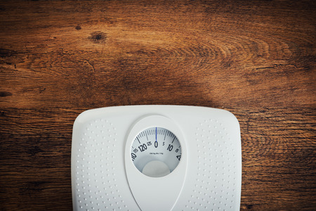 Foto de White scale on a wooden table top view, fitness and weight loss concept - Imagen libre de derechos