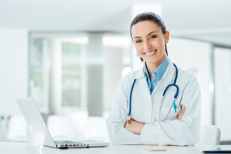 Foto für Confident female doctor sitting at office desk and smiling at camera, health care and prevention concept - Lizenzfreies Bild