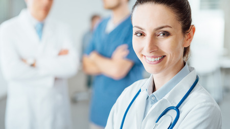 Photo for Professional female doctor smiling at camera and posing, medical staff working on background, selective focus - Royalty Free Image