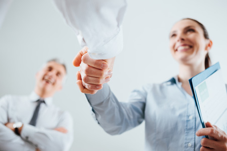 Foto de Confident business people shaking hands and woman smiling, recruitment and agreement concept - Imagen libre de derechos