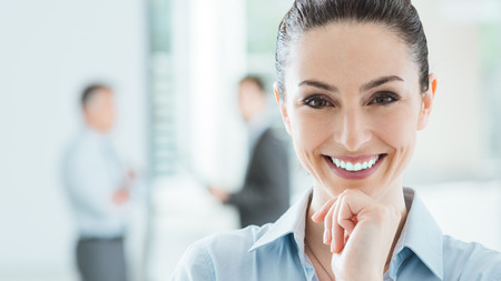 Foto de Confident beautiful smiling business woman in the office posing with hand on chin and looking at camera, office interior and business team on background, selective focus - Imagen libre de derechos