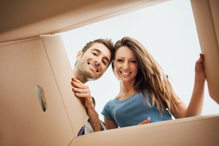 Photo pour Smiling young couple opening a carton box and looking inside, relocation and unpacking concept - image libre de droit