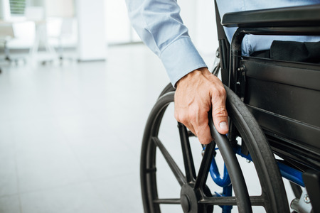 Foto de Businessman in wheelchair, hand on wheel close up, office interior on background - Imagen libre de derechos