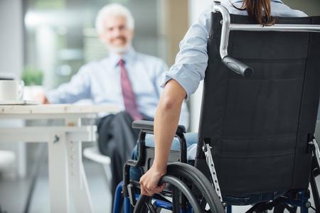 Foto de Disabled woman having a business meeting with a businessman rear view, selective focus - Imagen libre de derechos
