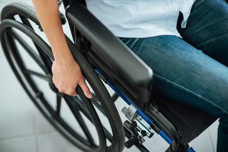 Foto de Woman in wheelchair's hand on wheel close up, disability and handicap concept - Imagen libre de derechos