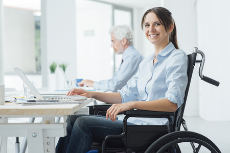 Foto de Confident happy businesswoman in wheelchair working at office desk and using a laptop, she is smiling at camera, disability overcoming concept - Imagen libre de derechos