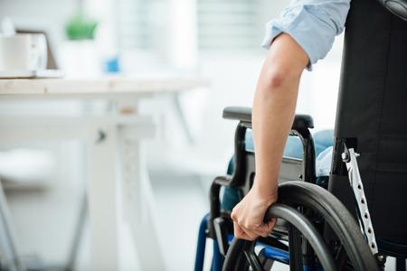 Foto de Woman in wheelchair next to an office desk, hand close up, unrecognizable person - Imagen libre de derechos