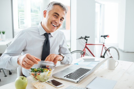 Photo pour Happy businessman opening his salad pack and having a lunch break at office desk - image libre de droit