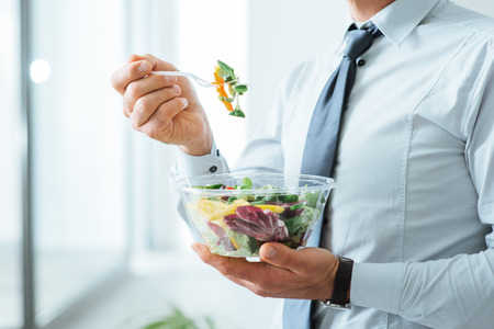 Foto de Businessman having a vegetables salad for lunch, healthy eating and lifestyle concept, unrecognizable person - Imagen libre de derechos