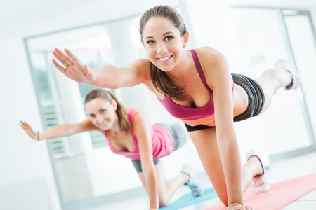 Photo pour Sporty young women at the gym doing pilates workout on a mat, fitness and healthy lifestyle concept - image libre de droit