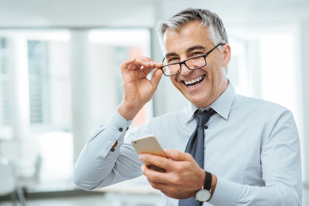 Foto für Smiling businessman with eyesight problems, he is adjusting his glasses and reading something on his mobile phone - Lizenzfreies Bild