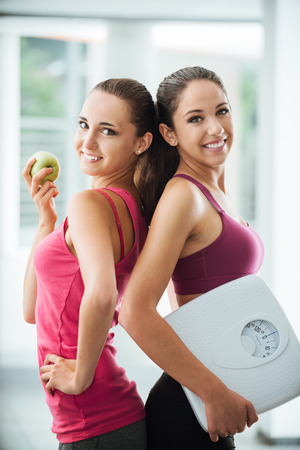Foto de Happy teenage girl friends holding an apple and a scale, they are posing and smiling at camera, fitness and weight loss concept - Imagen libre de derechos