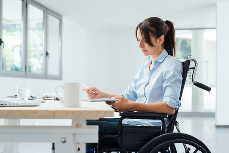 Foto de Confident disabled business woman in wheelchair working at office desk and checking paperwork - Imagen libre de derechos
