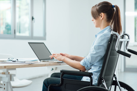 Foto de Young disabled business woman in wheelchair working at office desk and typing on a laptop, accessibility and independence concept - Imagen libre de derechos