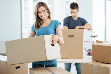 Photo for Young happy couple moving in their new house and unpacking boxes, she is carrying a carton box and smiling at camera - Royalty Free Image