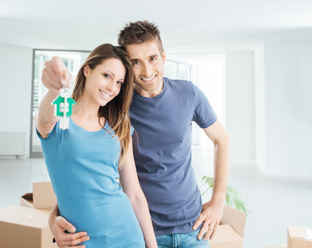 Foto de Young smiling couple holding their new house keys, real estate and relocation concept - Imagen libre de derechos