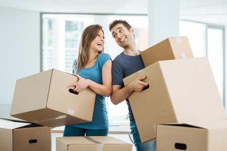 Foto per Happy couple staring at each other eyes and carrying boxes in their new house - Immagine Royalty Free