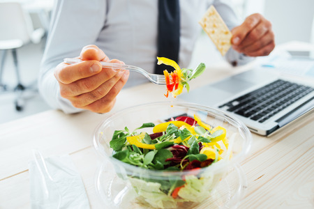 Foto de Businessman having a lunch break at desk, he is eating fresh salad and holding a cracker, unrecognizable person - Imagen libre de derechos