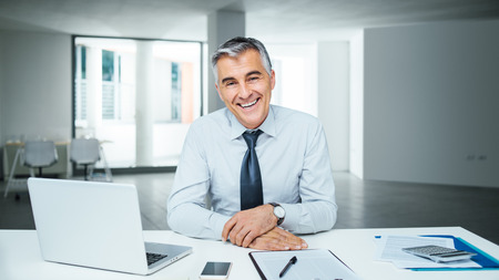 Foto de Confident handsome businessman sitting at office desk and smiling at camera - Imagen libre de derechos