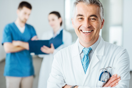 Photo for Confident doctor posing and smiling at camera and medical staff checking medical records on background - Royalty Free Image