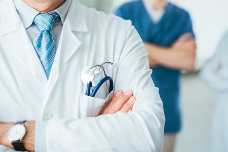 Photo pour Professional medical team posing, doctor's lab coat and stethoscope close up, selective focus - image libre de droit
