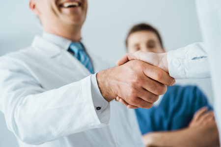 Photo pour Professional doctors handshaking at hospital, hands close up, agreement and hiring concept - image libre de droit