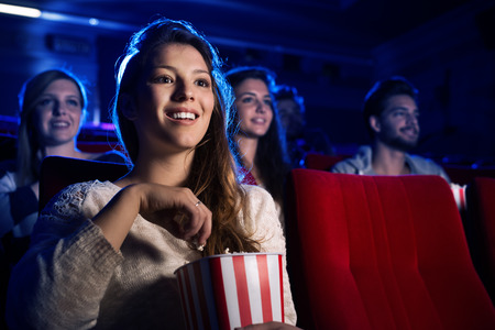 Photo for Young smiling woman watching a film in the movie theater and eating popcorn, entertainment and cinema concept - Royalty Free Image