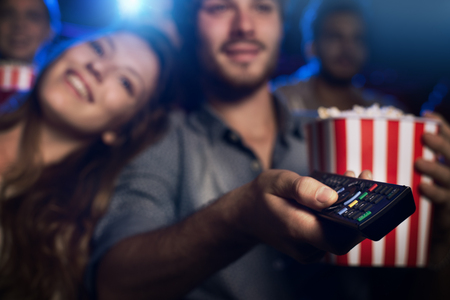 Photo pour Young man watching a movie with his girlfriend and pointing a remote control: cinema, entertainment and home theater concept - image libre de droit