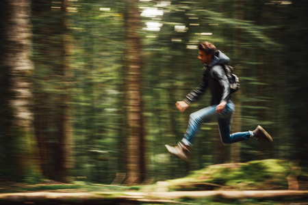 Foto de Hooded young man with backpack running in the forest - Imagen libre de derechos