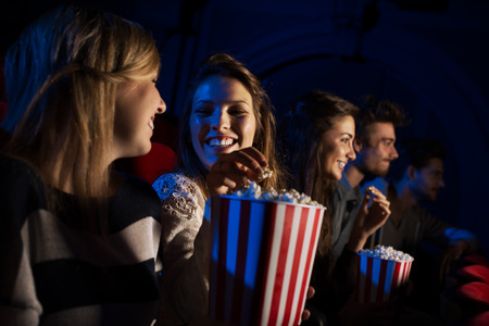Photo for Group of teenager friends at the cinema watching a movie together and eating popcorn, entertainment and enjoyment concept - Royalty Free Image