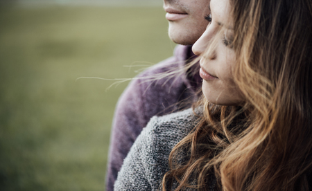 Photo pour Young loving couple outdoors sitting on grass, hugging and looking away, future and relationships concept - image libre de droit