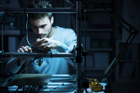 Foto de Young engineer working at night in the lab, he is adjusting a 3D printer's components, technology and engineering concept - Imagen libre de derechos
