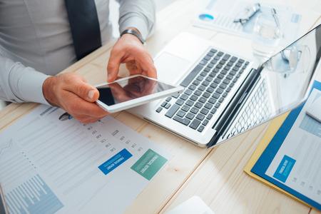 Foto de Professional businessman working at desk and using a touch screen tablet, technology and communication concept - Imagen libre de derechos