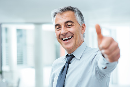Photo for Cheerful businessman thumbs up posing and smiling at camera - Royalty Free Image