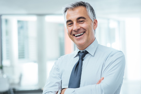 Photo pour Successful businessman posing with crossed arms and smiling at camera - image libre de droit