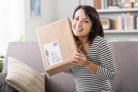 Foto de Smiling young woman at home on the couch, she has received a postal parcel, online shopping and delivery concept - Imagen libre de derechos