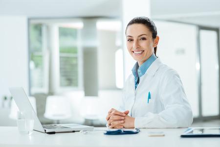 Foto de Female doctor working at office desk and smiling at camera, office interior on background - Imagen libre de derechos
