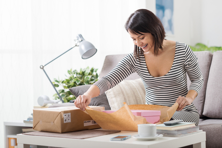 Photo for Happy excited woman at home, she has received a postal parcel and she is unboxing her gift, delivery and online shopping concept - Royalty Free Image