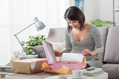Foto de Happy excited woman at home, she has received a postal parcel and she is unboxing her gift, delivery and online shopping concept - Imagen libre de derechos